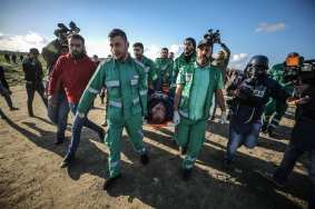 An injured press member is being carried away after Israeli forces attacked Palestinians during the Great March of Return demonstrations in Gaza on 18 January 2019 [Ali Jadallah/Anadolu Agency]
